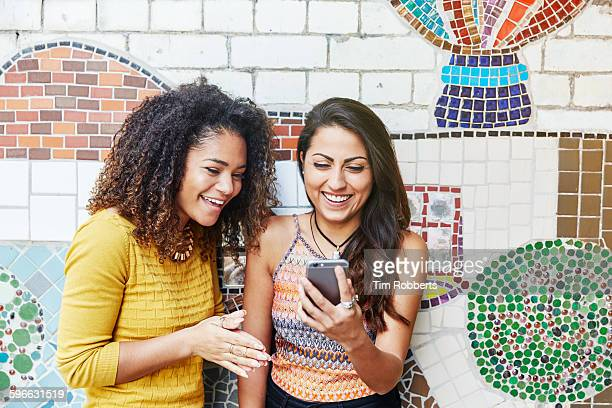 Friends with smartphone in front of mosaic wall