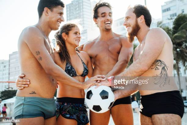 Friends with Soccer Ball holding hands in unity, Rio de Janeiro, Brazil