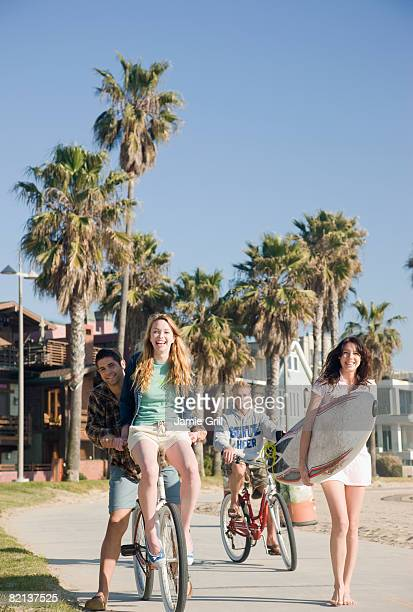 Friends with surfboard and bicycles at beach
