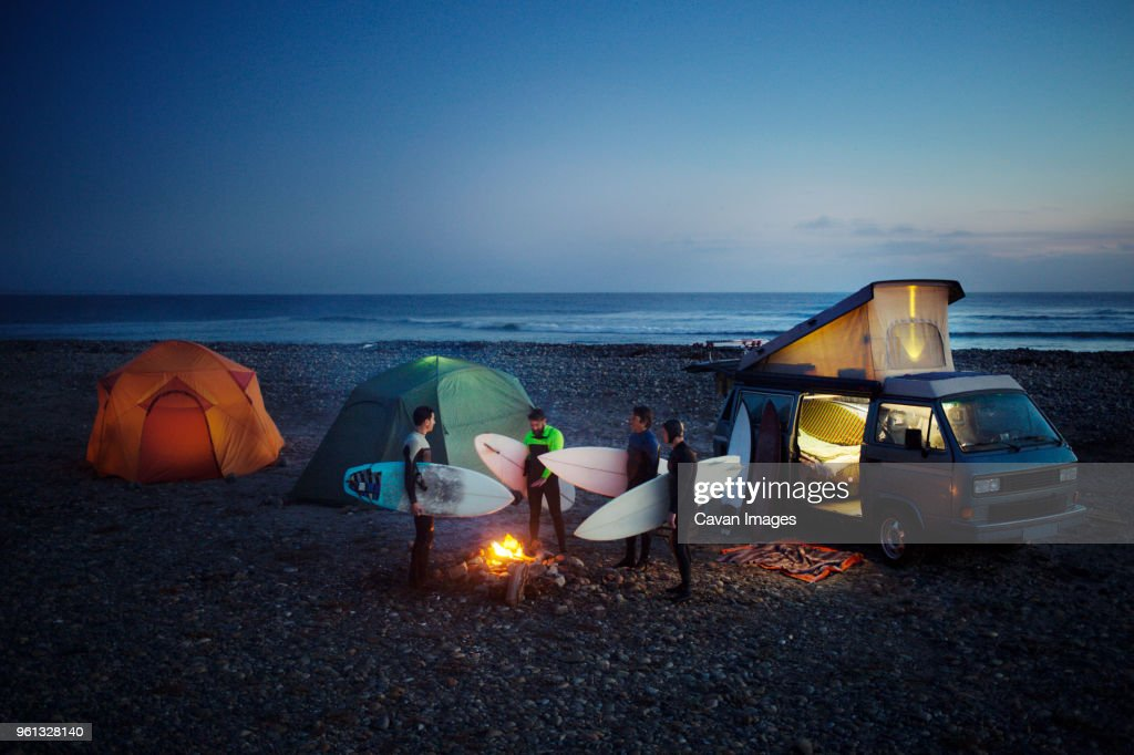 Friends with surfboard camping at beach against sky : Stock Photo