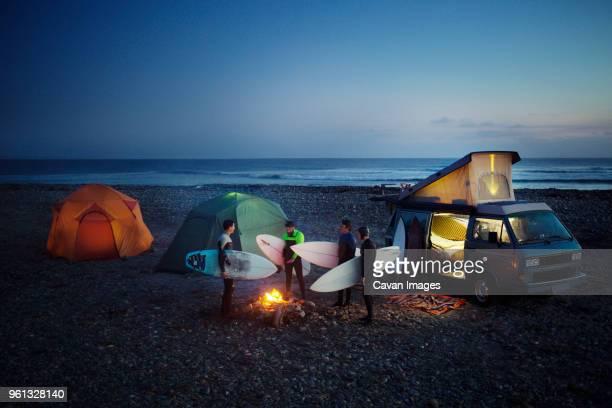 friends with surfboard camping at beach against sky - halbinsel niederkalifornien stock-fotos und bilder