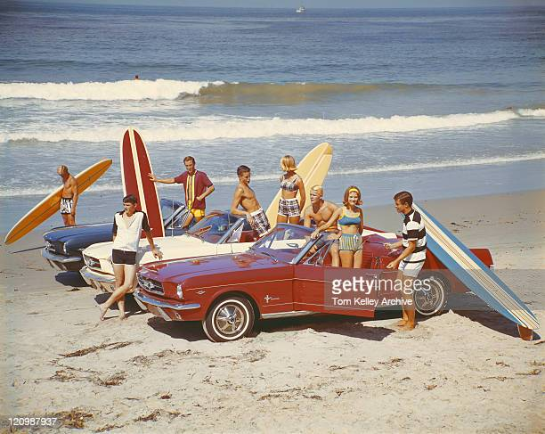 Friends with surfboards in car on beach