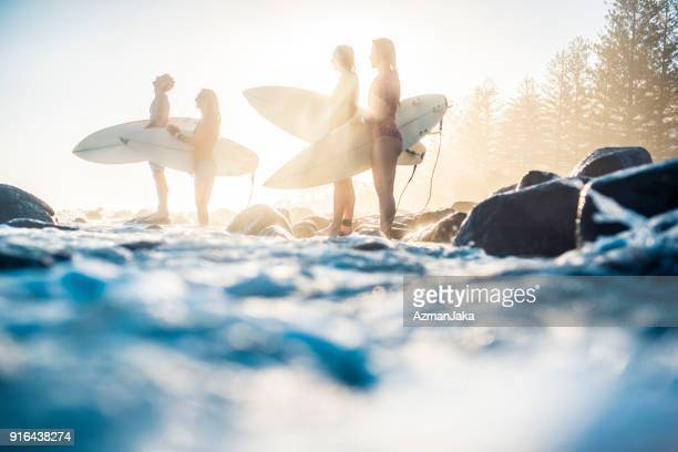 Friends with surfboards standing in the ocean