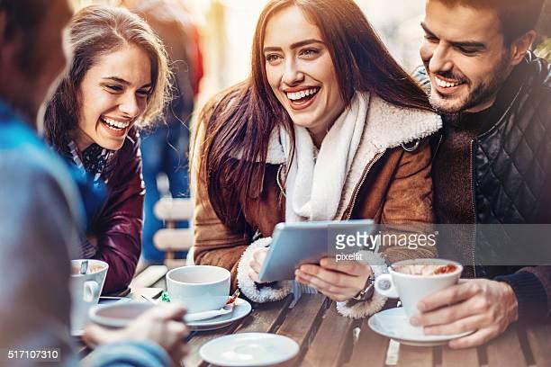 Amigos con Tablet y bebidas calientes