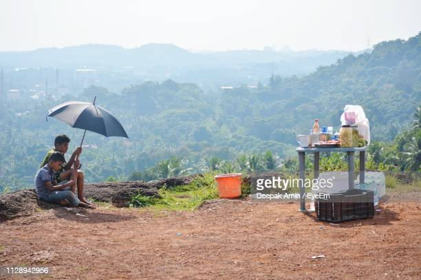 Friends With Umbrella Sitting On Mountain Against Sky During Sunny Day