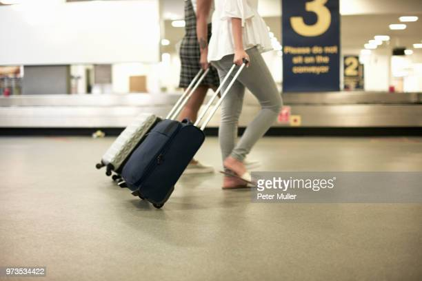 friends with wheeled suitcases in airport - wheeled luggage stock photos and pictures