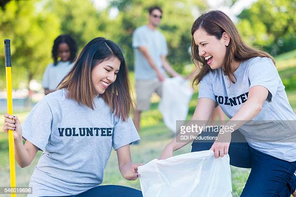 Friends work with their neighbors to clean up park