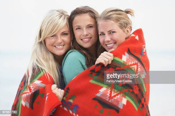 friends wrapped in colorful blanket - climat stock pictures, royalty-free photos & images