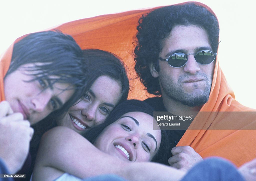 Friends wrapped in orange blanket, close-up. : Stockfoto