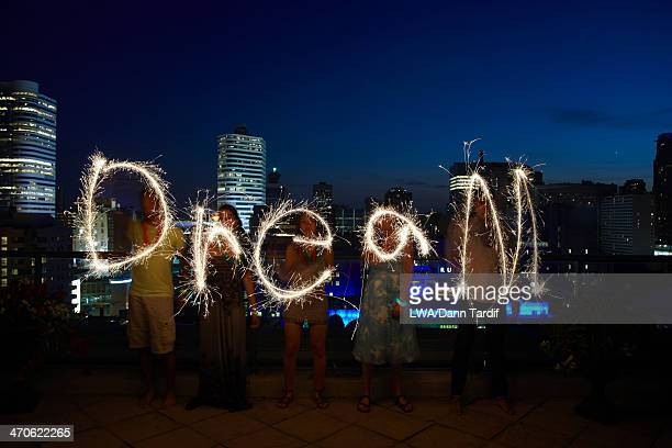 Friends writing 'dream' with sparklers on urban rooftop