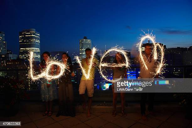 Friends writing 'love' with sparklers on urban rooftop