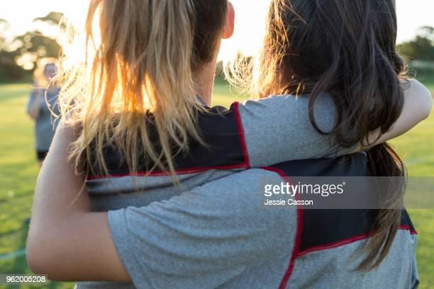 friendship on the sports field - two female sports players embrace - sport of cricket imagens e fotografias de stock