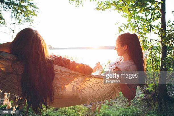 friendship: rear view, two young woman relax in a hammock