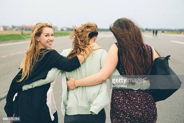 friendship: three carefree young women with tousled hair walking forward