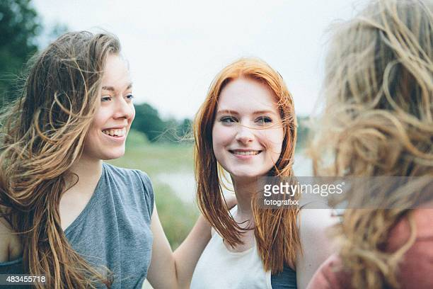 friendship: three cheerful laughing young women having fun together outdoors - lake auburn stock photos and pictures