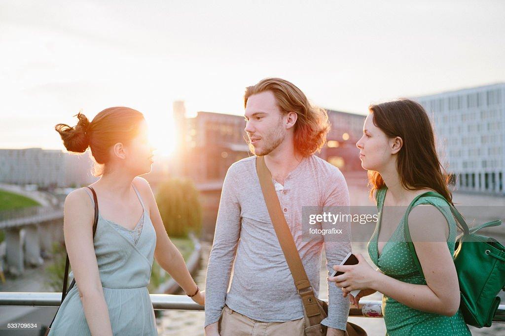 Amicizia: Tre giovani adulti in piedi insieme e parlando : Foto stock