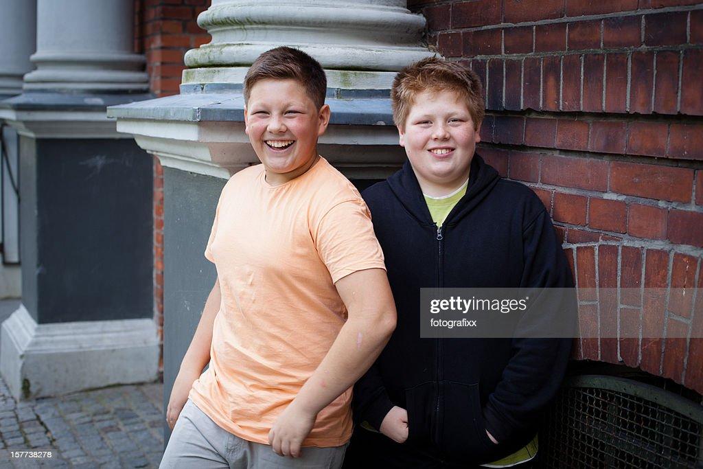 Amizade: Dois meninos adolescentes com excesso de peso em frente a escola. : Foto de stock