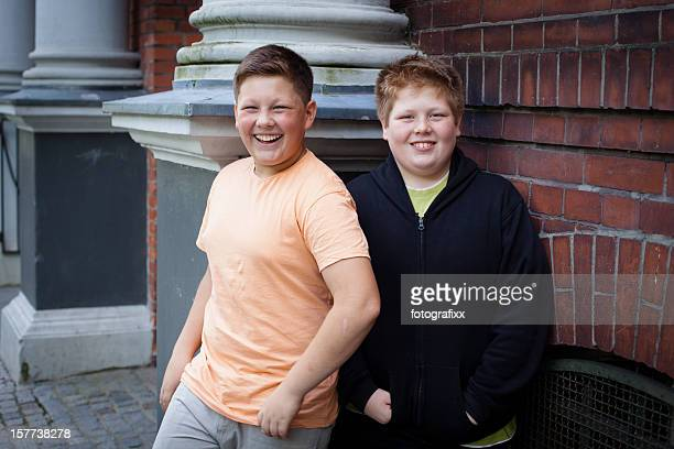 friendship: two overweight teenage boys in front of their school - chubby boy stock photos and pictures