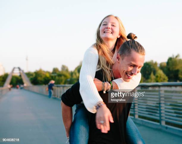 friendship: young couple has fun with piggyback, summer in berlin - teenage couple stock photos and pictures