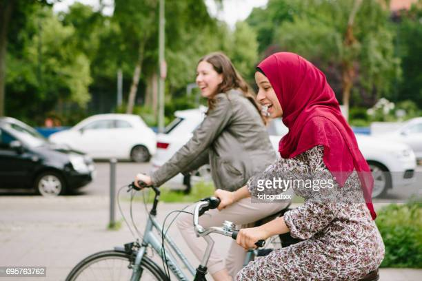Friendship: young muslim woman with hijab and friend ride bicycle