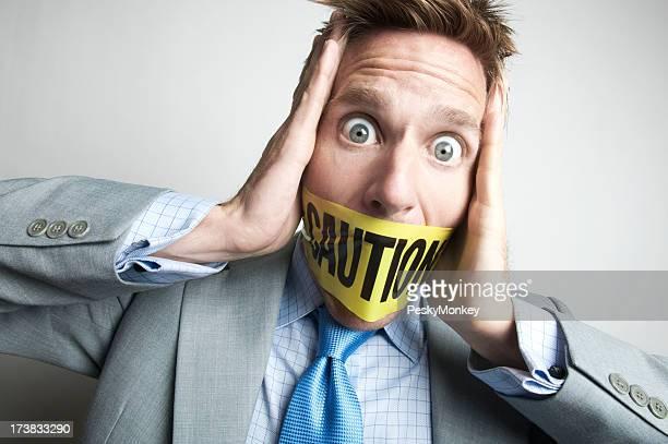 Angst Geschäftsmann gegebenenfalls einen Maulkorb tragen. Mit Vorsicht Tape
