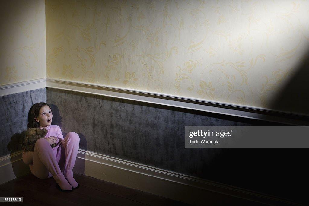 frightened girl in pajamas cowering in corner : Stock Photo