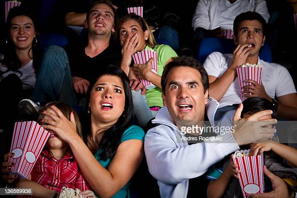 frightened hispanic family watching film in movie theater - scary movie stock photos and pictures