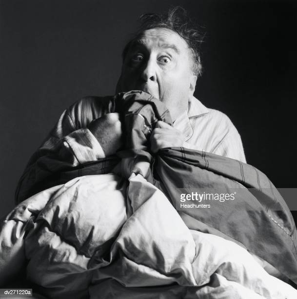 frightened man in bed holding blanket to face - headhunters stock pictures, royalty-free photos & images