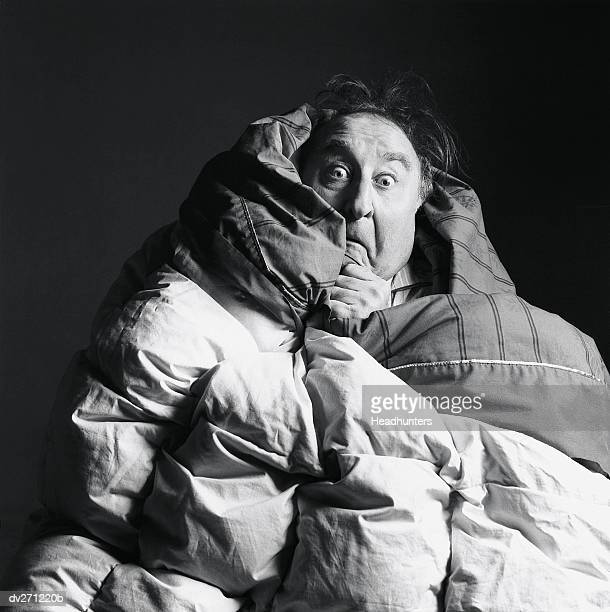 frightened man with blankets wrapped around himself - headhunters stock pictures, royalty-free photos & images