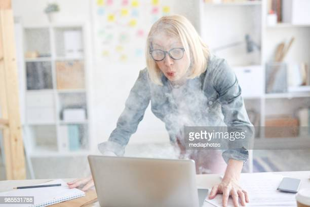 frightened middle-aged woman with blond hair having problem with laptop: she blowing at computer to put out it in office - extinguishing stock pictures, royalty-free photos & images
