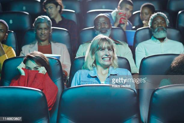 frightened multi-ethnic men and women watching horror movie in cinema hall of theater - film industry stock pictures, royalty-free photos & images