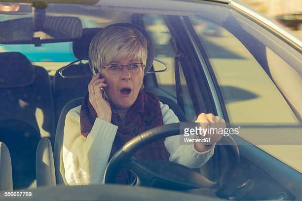 Frightened senior woman in car on cell phone