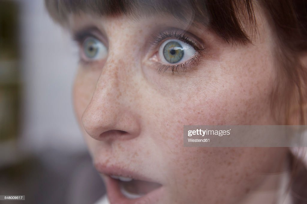 Frightened woman behind window : Stock-Foto