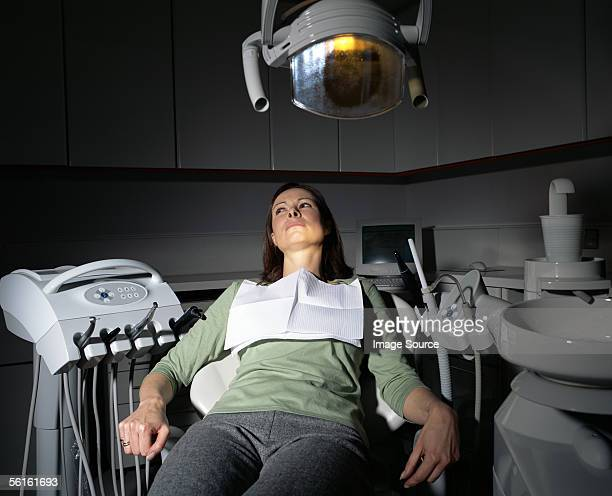 frightened woman in dentist's chair - dental fear stock pictures, royalty-free photos & images