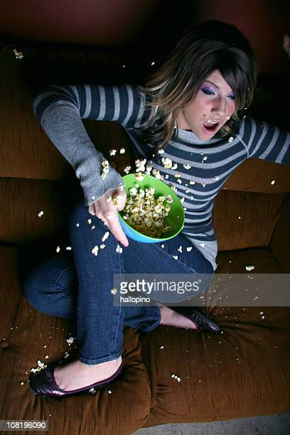 frightened woman spilling popcorn on couch - horror movie stock pictures, royalty-free photos & images