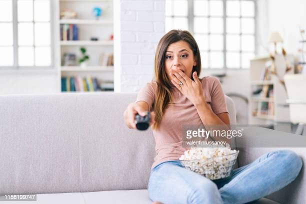 a frightened woman watching tv at home - redoubtable film stock photos and pictures