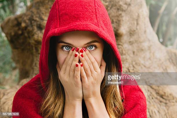 frightened woman wearing red hood covering face with her hands - caperucita roja fotografías e imágenes de stock