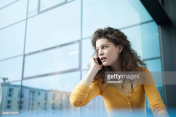 Frightened young woman on the phone at the window