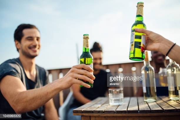 frineds toasten bierflaschen auf party auf dem dach - feierabend stock-fotos und bilder