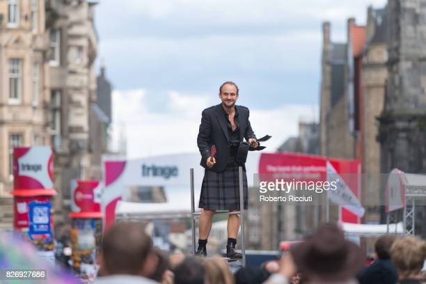 Fringe participant promotes his show entertaining people on the Royal Mile during the third day of the annual Edinburgh Fringe Festival on August 6...