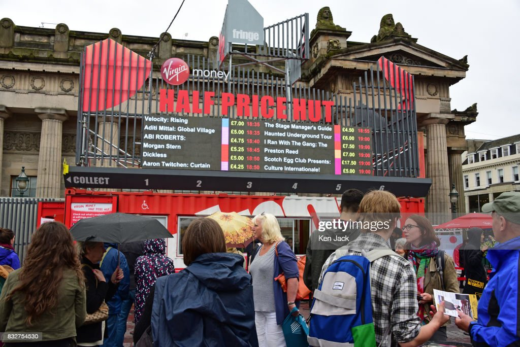 Fringe-goers study shows on offer at reduced prices at the 'Half Price Hut' booking office during the Edinburgh Festival Fringe, on August 16, 2017 in Edinburgh, Scotland. The Fringe is celebrating its 70th year, and this year hosts over three thousand shows and more than 50,000 performances.