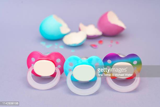 frisch geschlüpft: lgbtq schnuller in regenbogenfarben mit eierschale für drillinge - baby shower stock pictures, royalty-free photos & images