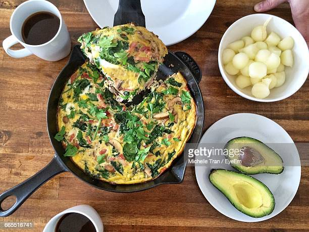 Frittata With Halved Avocado And Black Coffee On Wooden Table
