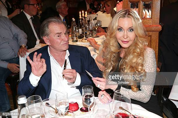 Fritz Wepper gives Dolly Buster his business card during the VIP premiere of Schubeck's Teatro at Spiegelzelt on November 3 2016 in Munich Germany