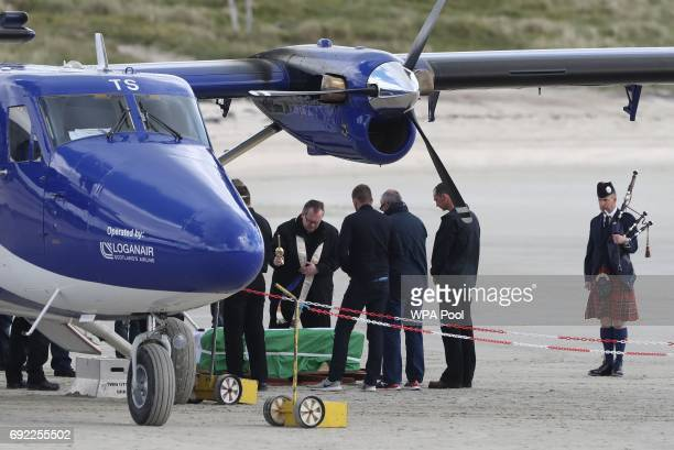 FrJohn Paul MacKinnon blesses the coffin of Eilidh MacLeod draped in the Barra flag at Traigh Mhor beach after it arrived by chartered plane on June...