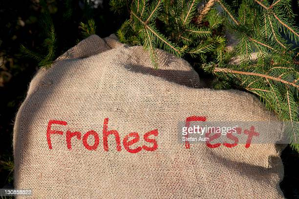 frohes fest or merry christmas, red lettering on a sack, spruce branches - captions stock photos and pictures