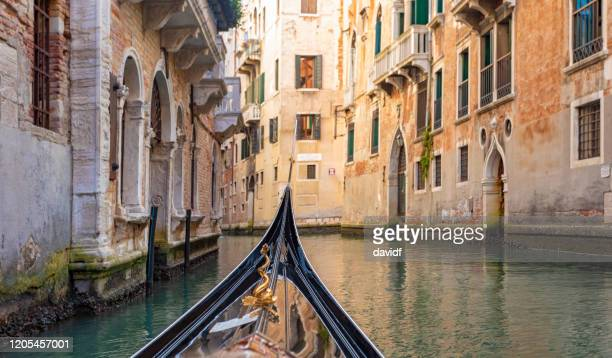 pov from a gondola on a canal in venice, italy - gondola traditional boat stock pictures, royalty-free photos & images