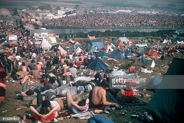 From a hillside camping area pop fans look down on the jammed area behind a fence during the Isle of Wight Festival