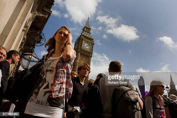From a very low viewpoint we see crowds of British citizens who to and fro beneath the Gothic tower of Big Ben in Parliament Square London at almost...