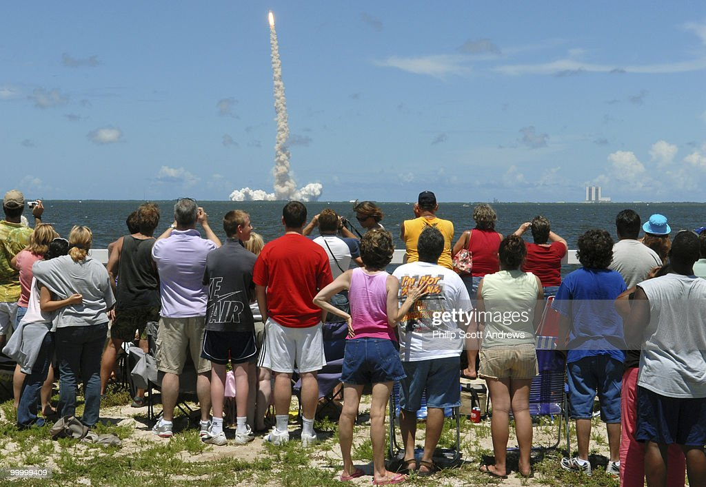 From across the Indian River spectators watch as the Space Shuttle Discovery lift off from Kennedy Space Center. The mission, originally scheduled for July 1 was delayed for three days do to bad weather and launched on the 4th of July, the first time the Shuttle had been launched on the holiday.